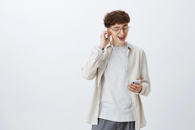 Беззаботный подросток позирует у белой стены