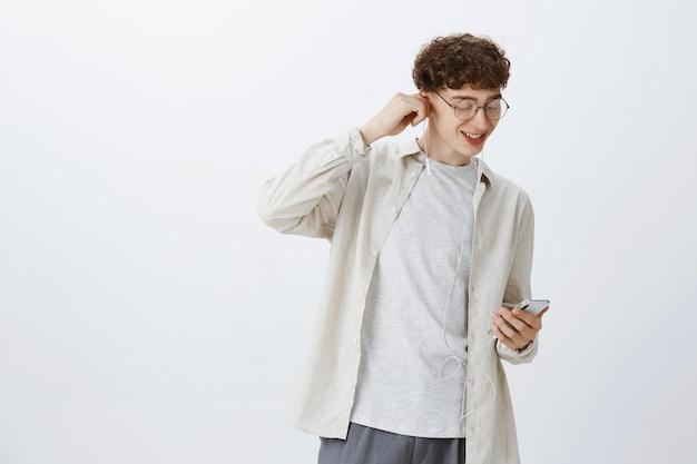 Ragazzo adolescente spensierato in posa contro il muro bianco
