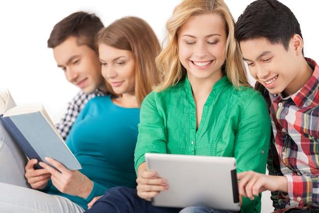 Беззаботные подростки. группа студентов, проводящих время вместе, сидя на белом