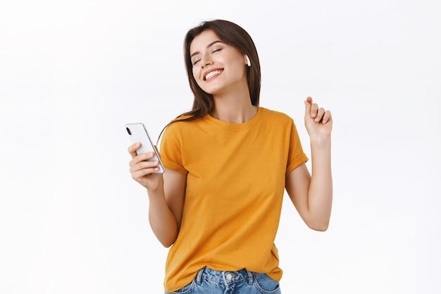 노란색 티셔츠를 입은 평온하고 현대적인 세련된 여성은 새로운 무선 이어폰으로 멋진 비트를 즐기고, 손을 들고 춤을 추고, 편안한 자세로, 스마트폰을 들고 눈을 감고 웃고 있습니다.