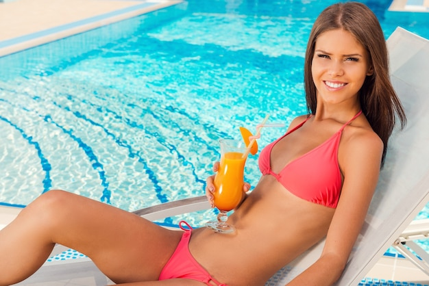 Carefree time poolside. top view of beautiful young woman in bikini drinking cocktail and smiling while relaxing in deck chair near the pool