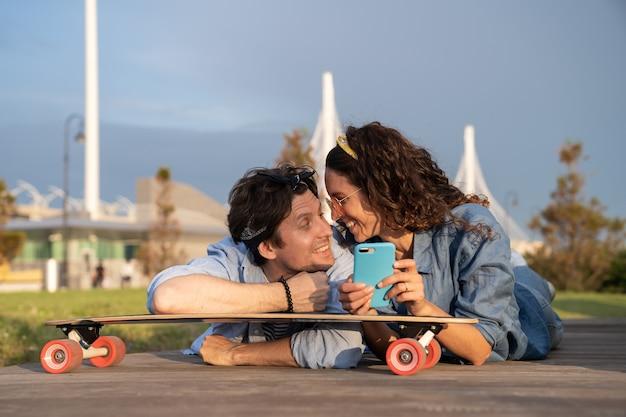 のんきなトレンディなカップルが屋外でインターネットをオンラインサーフィンし、ロングボードに横たわっている携帯電話のインターネットを使用します