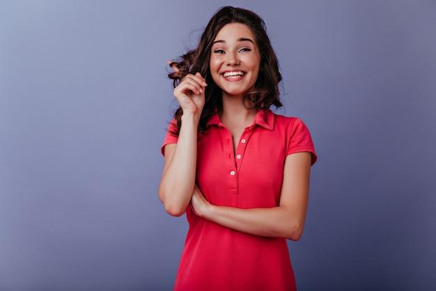 光沢のある巻き毛で遊んで笑っているのんきな白人少女。紫色の壁に立っている赤いカジュアルな服装でゴージャスな白人女性。