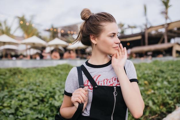 通りでポーズをとっている間、茶色の髪ののんきな白人の女の子が目をそらしている。リゾートシティで週末を過ごすスタイリッシュなtシャツを着た見事なヨーロッパの女性の屋外ショット。