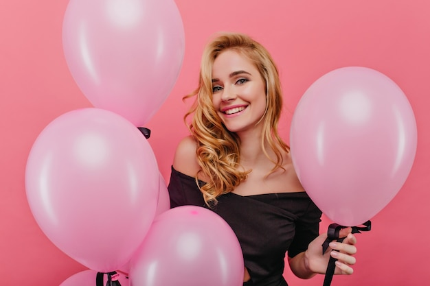 핑크 풍선 근처 포즈 진심 으 미소로 평온한 백인 소녀. 생일을 축하하는 물결 모양의 머리를 가진 즐거운 젊은 여자의 실내 사진.