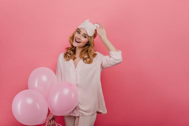 분홍색 벽에 웃으면 서 아이 마스크를 만지고 평온한 백인 여자. 풍선 파티를 즐기는 잠 옷에 예쁜 생일 소녀.