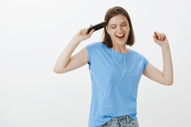 Беззаботная женщина танцует и поет, слушает музыку через наушники на мобильном телефоне