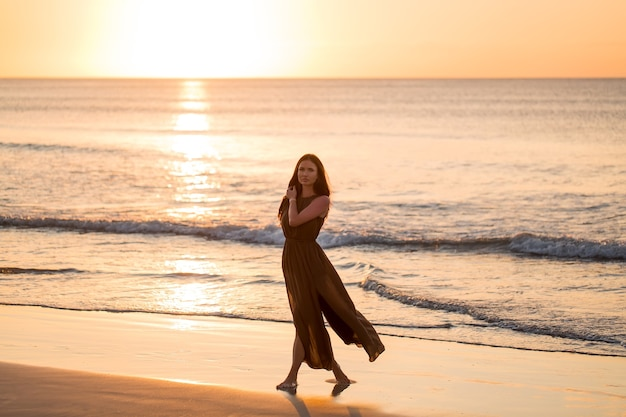 Беззаботная женщина, наслаждаясь закатом на пляже. счастливый образ жизни