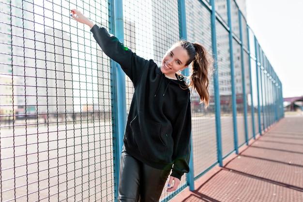 Беззаботная женщина развлекается на детской площадке в теплый ветреный день