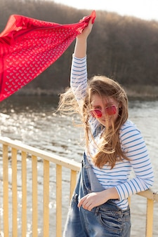 Carefree woman holding scarf in the wind by the lake