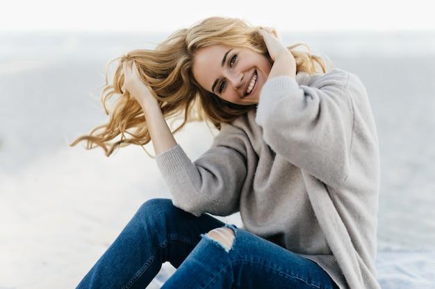 해변에서 그녀의 머리를 만지고 부드러운 스웨터에 평온한 여자. 가을 해변에서 쉬고 사랑스러운 백인 여자의 야외 초상화.