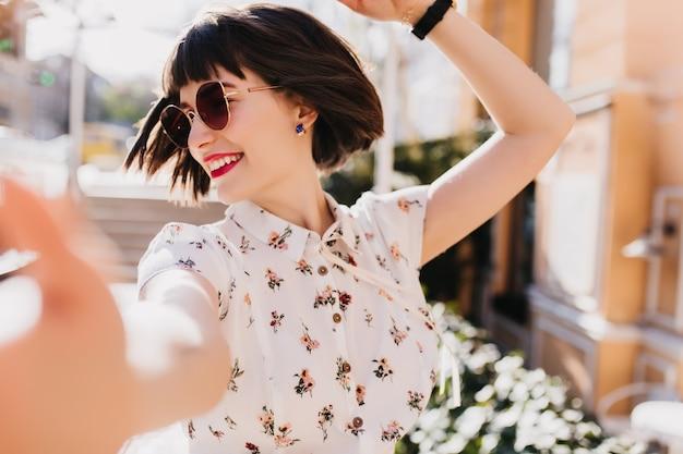 路上で踊るスタイリッシュなブラウスののんきな女性。ぼやけた街で自分撮りをする短い暗褐色の髪の女性モデルを笑う。