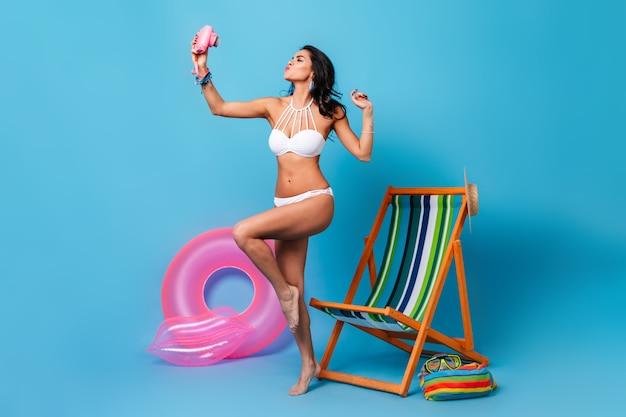 Беззаботная женщина в купальнике, делающая селфи