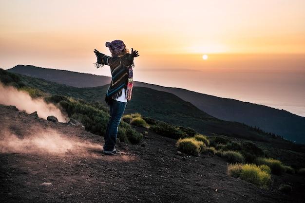 夕日の美しい景色を眺めながら山の斜面に腕を伸ばした暖かい服を着たのんきな女性。休暇中に自然を探索する女性ハイカー