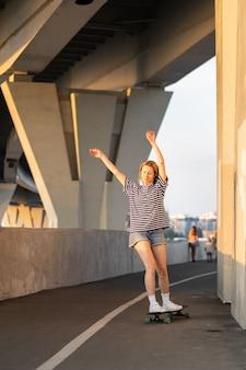 자유를 즐기는 여름 석양에 롱보드 응원 스케이팅을 타고 평온한 중년 여성