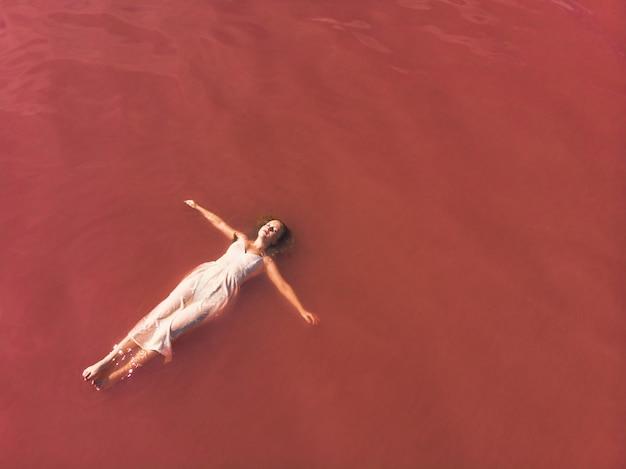 Беззаботная женщина на отдыхе, наслаждаясь в розовой воде озера