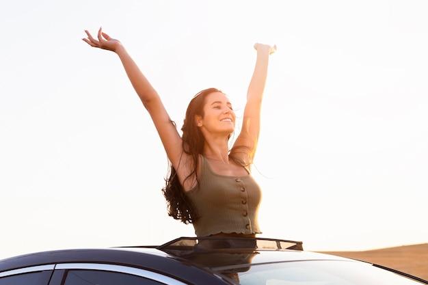屈託のない女性が夕日に彼女の車からポーズ