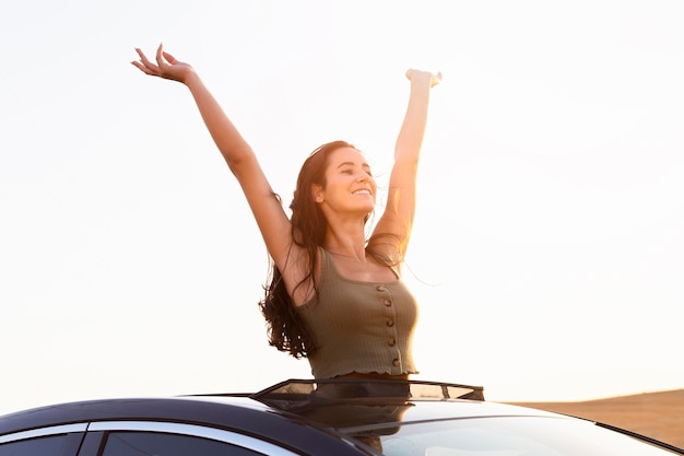 Carefree woman posing from her car in the sunset