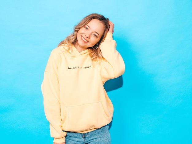 Carefree woman posing near blue wall in studio. positive model having fun