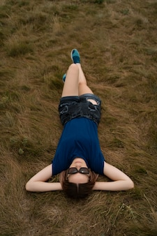 Carefree woman relaxing on the grass during sunny summer day wearing glasses and shorts.