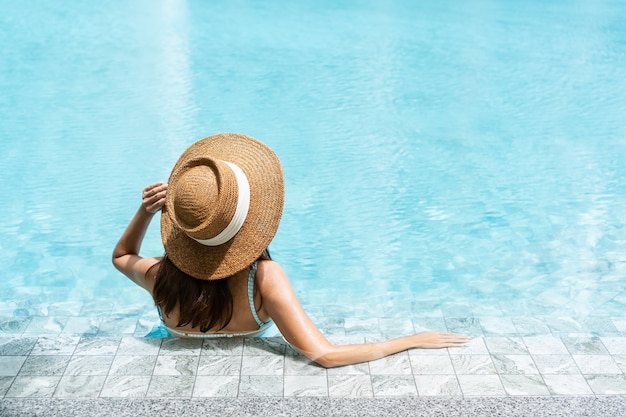 Carefree woman relaxing in swimming pool. summer and holiday concept. rear view, close up