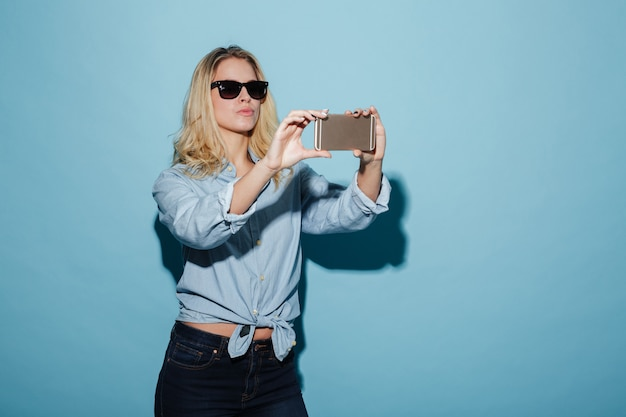 Carefree woman in shirt and sunglasses making selfie on smartphone