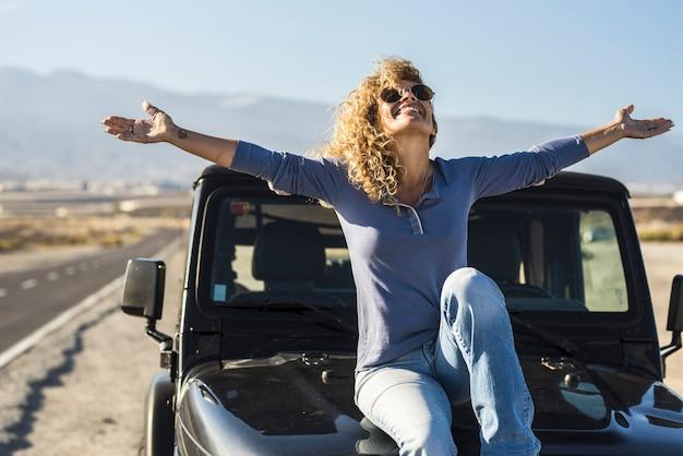 道端に駐車した車のボンネットに座っているのんきな女性。空の下で車のボンネットに座って楽しんで腕を広げて陽気な若い女性 Premium写真