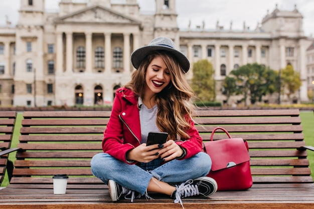 Carefree woman sitting on wooden bench and texting message with charming smile
