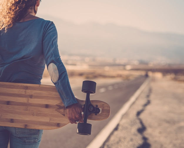 長いアスファルト道路の脇に彼女の背中の後ろに木製のロングボードを立って保持しているのんきな女性。ロングボードを手に、道路を前に進む意欲的な女性