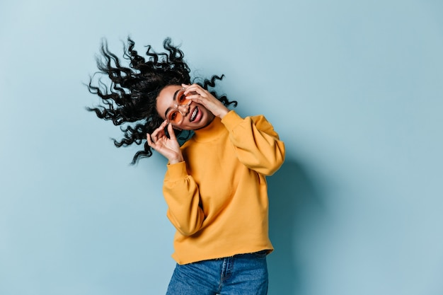 Carefree woman in sunglasses dancing on blue wall