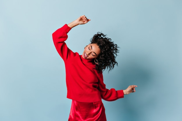 Carefree woman in total red dancing and waving hands