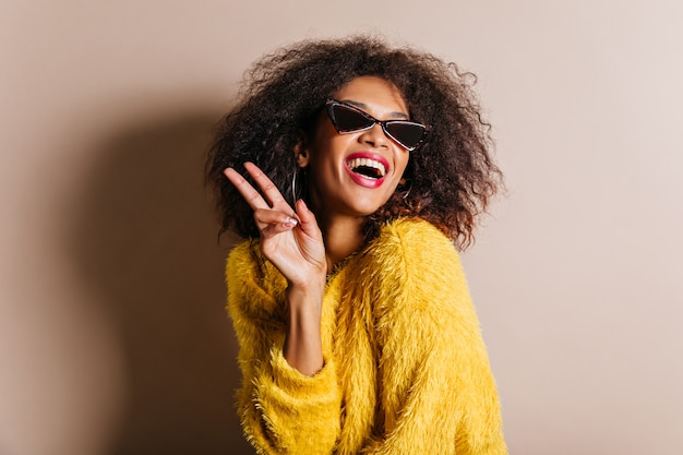 Carefree woman with funny hairstyle enjoying photoshoot