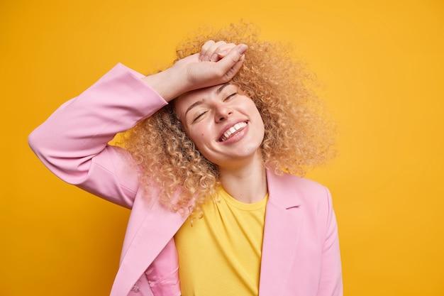 La donna spensierata con i capelli ricci naturali sorride positivamente tiene gli occhi chiusi la mano sulla fronte vestita con abiti formali esprime felicità isolata sul muro giallo vivido. concetto di felicità