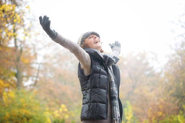 Carefree woman with outstreched arms in autumn