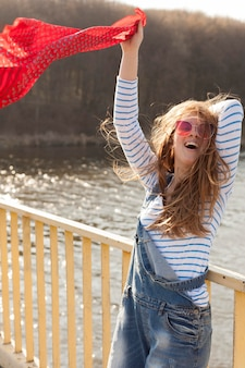 Carefree woman with sunglasses holding scarf in the wind by the lake