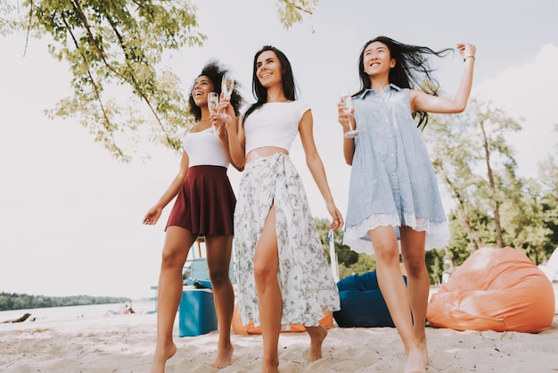 Carefree women drinking champagne at beach party