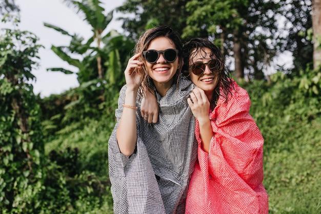 자연에 자매를 포용하는 분홍색 비옷에 평온한 여성. 숲에서 재미 선글라스에 긍정적 인 여성의 야외 사진.