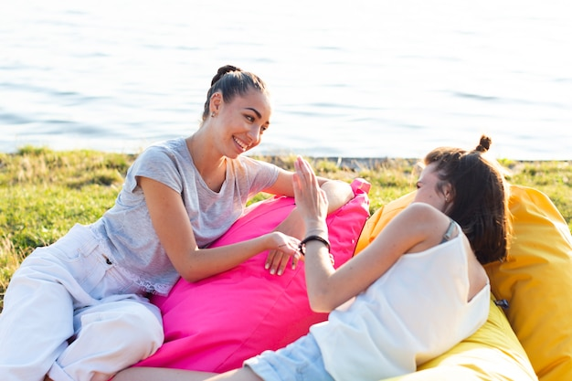 Carefree women playing on colorful beanbags