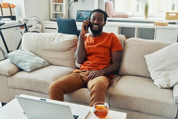 평온한 젊은 아프리카 남자가 전화로 이야기하고 집에서 시간을 보내는 동안 웃고