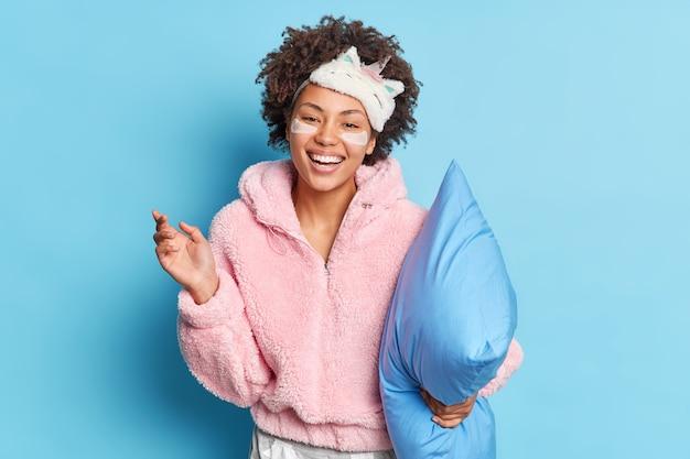 のんきな若いアフロアメリカ人女性は、寝間着を着て広くカメラの笑顔を見て幸せそうに見えます寝る準備をします青い壁に隔離された枕を保持します