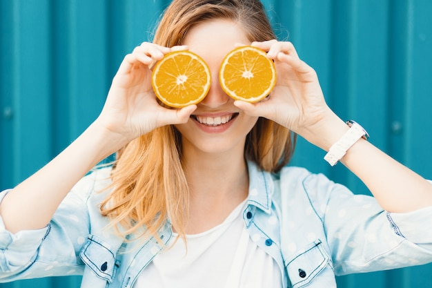 彼女の目の上の眼鏡の代わりにオレンジの2つの半分を使用して屈託のない美しい少女 無料写真
