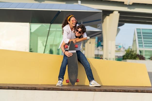 のんきな若いカップルは楽しいガールフレンドがボーイフレンドの恋人の女の子と男のスケートボーダーをピギーバックしています