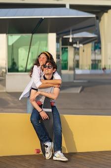 평온한 젊은 한 쌍 이 재미 여자 친구 편승 남자 친구 연인 소녀와 사람 스케이트 보더