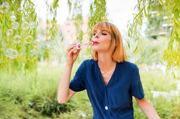 여름 공원의 푸른 나무 가지 아래 서서 비누 방울을 부는 파란 드레스를 입고 염색한 머리를 한 평온한 젊은 여성