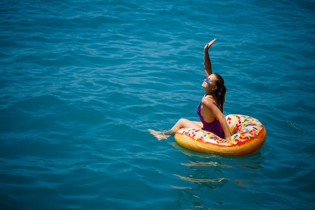 Carefree young girl woman enjoying a relaxing day at sea, floating on an inflatable ring. sea vacation concept