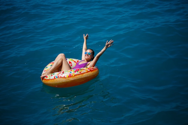 Carefree young girl woman enjoying a relaxing day at sea, floating on an inflatable ring, top view. sea vacation concept