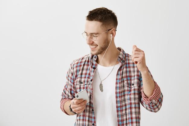 彼の電話とイヤホンでポーズをとる眼鏡をかけたのんきな若い男