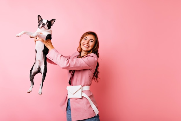 Carefree young lady holding black french bulldog with sincere smile. indoor portrait of joyful girl playing with dog on pastel.