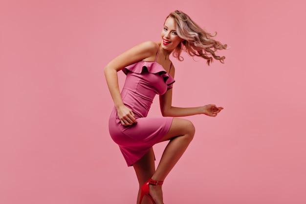 幸せに笑ってトレンディなピンクの衣装でのんきな若い女性