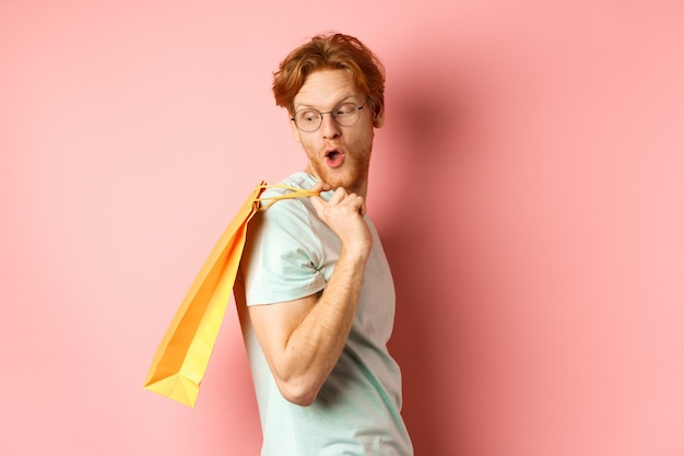 Carefree young man with red hair and glasses, walking with shopping bag, looking behind his shoulder with amazed expression, standing over pink background.